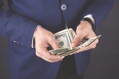 Młody biznesowego mężczyzny ręki mienia pieniądze na ciemnym tle fotografia royalty free