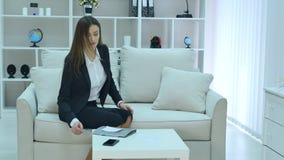 Młody biznesowej kobiety obsiadanie na leżance z notatnikiem w rękach zdjęcie wideo