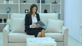 Młody biznesowej kobiety obsiadanie na leżance z notatnikiem w rękach zbiory wideo