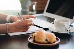 Młody biznesowej kobiety obsiadanie w kawiarni i brać notatkach w notatniku zdjęcia stock