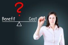 Młody biznesowej kobiety writing koszt i korzyść porównujemy na równowaga barze niebieska tła zdjęcia stock
