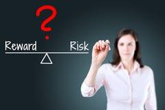 Młody biznesowej kobiety writing pytanie z ryzykiem porównuje nagradzać na równowaga barze niebieska tła fotografia royalty free