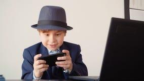 Młody biznesowy mężczyzna bawić się w mobilnych grach przy miejsce pracy w biznesowym biurze Chłopiec w garnituru i kapeluszu obs zbiory wideo