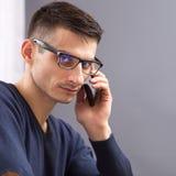 Młody biznesowy mężczyzna mówi na telefonie w szkłach Obrazy Royalty Free