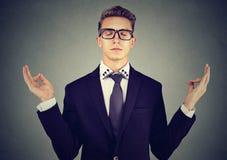 Młody biznesowy mężczyzna medytuje relaksować z oczami zamykającymi zdjęcie stock