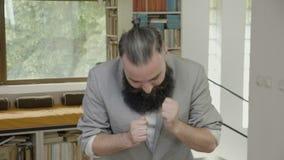 Młody biznesowy mężczyzna ono uśmiecha się wokoło wyrażać jego szczęście i tanczy w biurze z brodą - zdjęcie wideo