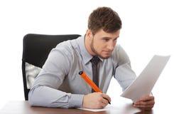Młody biznesowy mężczyzna pisze notatce obraz stock