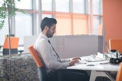 Młody biznesowy mężczyzna pracuje na komputerze stacjonarnym Zdjęcia Stock