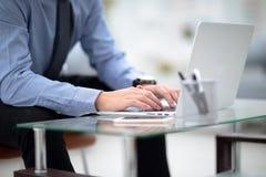 Młody biznesowy mężczyzna pracuje na laptopie przy jego biurkiem w biurze, na widoku profilu przeciw okno Obrazy Stock