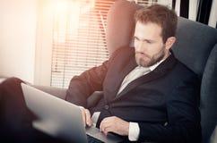 Młody biznesowy mężczyzna pracuje od domu z laptopem Zdjęcie Stock