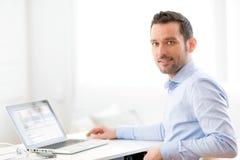 Młody biznesowy mężczyzna pracuje w domu na jego laptopie Fotografia Stock