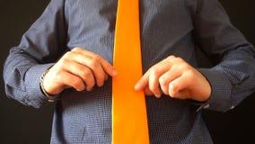 Młody biznesowy mężczyzna prostuje jego pomarańczowych spojrzenia w lustrze i krawat w domu zbiory
