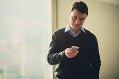 Młody biznesowy mężczyzna przy biurem w korporacyjnym budynku używać jego telefon komórkowego Zdjęcia Royalty Free
