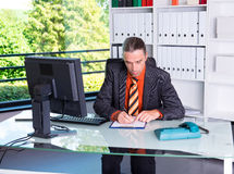Młody biznesowy mężczyzna przy jego biurka writing Obrazy Stock