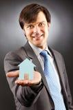 Młody biznesowy mężczyzna trzyma modela dom na jego palmie Fotografia Royalty Free
