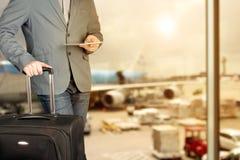 Młody biznesowy mężczyzna używa cyfrową pastylkę z bagażem w lotnisku fotografia royalty free
