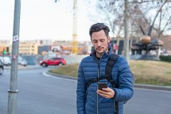 Młody biznesowy mężczyzna w ulicie z telefonem komórkowym i niebieską marynarką obrazy stock