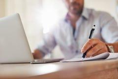 Młody biznesowy mężczyzna wręcza writing notatki Fotografia Royalty Free