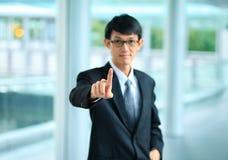 Młody biznesowy mężczyzna wskazuje z jego palcem w kostiumu Zdjęcia Royalty Free