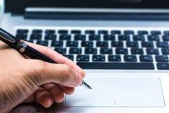 Młody biznesowy ręki writing w laptopie Fotografia Stock