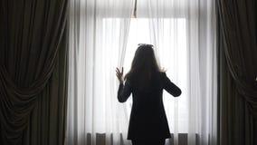 Młody bizneswoman odsłania zasłony patrzeć w okno zbiory