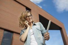 Młody bizneswoman ono uśmiecha się podczas gdy dzwoniący na telefonu komórkowego mienia laptoip w ręce Zdjęcie Stock