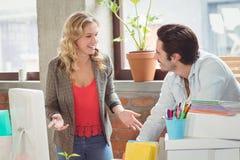 Młody bizneswoman opowiada męski kolega w biurze Zdjęcia Stock