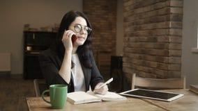 Młody bizneswoman opowiada telefonem i spojrzeniami na ekranie cyfrowa pastylka zbiory