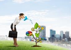 Młody bizneswoman outdoors nawadnia rysującego wzrostowego pojęcie z puszką Zdjęcie Stock