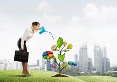 Młody bizneswoman outdoors nawadnia rysującego wzrostowego pojęcie z puszką Obrazy Stock