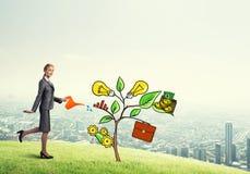 Młody bizneswoman outdoors nawadnia rysującego wzrostowego pojęcie z puszką Zdjęcia Royalty Free