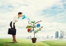 Młody bizneswoman outdoors nawadnia rysującego wzrostowego pojęcie z puszką Fotografia Stock