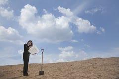 Młody bizneswoman patrzeje projekt obok łopaty po środku pustyni Zdjęcie Royalty Free