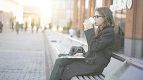 Młody bizneswoman pije kawę z laptopem, ulica Fotografia Royalty Free