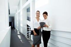 młody bizneswoman pracuje na dotyka ochraniaczu podczas gdy jej ufny partnera stać pobliski i uśmiechnięty Zdjęcia Stock