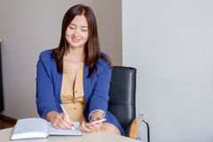 Młody bizneswoman pracuje przy biurkiem w biurze, brać notatkę w ogłoszenie towarzyskie kalendarz, ono uśmiecha się fotografia royalty free