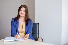 Młody bizneswoman pracuje przy biurkiem w biurze, brać notatkę w ogłoszenie towarzyskie kalendarz, ono uśmiecha się fotografia stock