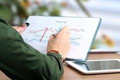Młody bizneswoman pracuje w biurze, siedzący przy jej biurkiem, analizujący dane w grafika, wskazuje piórem fotografia royalty free