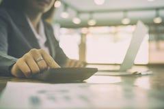 Młody bizneswoman pracuje z kalkulatorem, biznesowy dokument a fotografia royalty free
