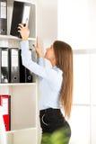 Młody bizneswoman Przed półkami Z segregatorami Fotografia Stock