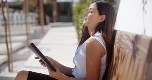 Młody bizneswoman relaksuje na plenerowej ławce zdjęcie wideo
