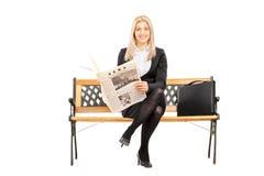 Młody bizneswoman sadzający na ławki mienia gazecie Zdjęcie Royalty Free
