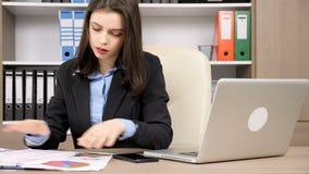 Młody bizneswoman sprawdza niektóre w jej biurze tapetuje zdjęcie wideo