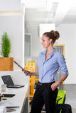 Młody bizneswoman trzyma pastylkę z listą zadania w nowożytnym jaskrawym biurze Biznesowy pojęcie biurowa praca Zdjęcia Royalty Free