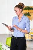 Młody bizneswoman trzyma pastylkę z listą zadania w nowożytnym jaskrawym biurze Biznesowy pojęcie biurowa praca Zdjęcie Stock