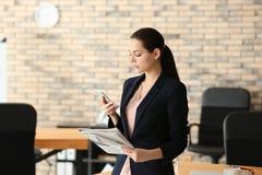 Młody bizneswoman z telefonem komórkowym i gazetą w biurze obrazy stock