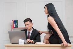 Młody bizneswomanu obsiadanie na stołowym i flirtować Zdjęcia Stock
