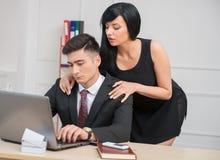 Młody bizneswomanu obsiadanie na stołowym i flirtować Obrazy Royalty Free