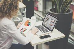 Młody bizneswomanu obsiadanie przy biurkiem i działaniem, na stołowym laptopie z wykresami, diagramami, mapami na ekranie i smart zdjęcie royalty free