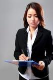 Młody bizneswomanu writing na schowku podczas gdy myśleć Zdjęcia Stock